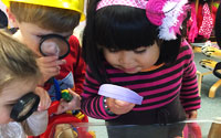 Explore | Children looking through magnifying glasses